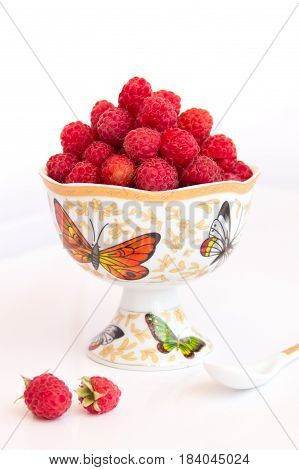 Still life with raspberries in a vase. A photo in a light key. Raspberries in the vase and a couple of berries on the table.