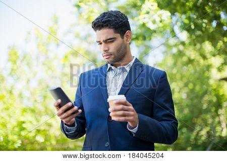 Businessman holding disposable coffee cup and using mobile phone in a park