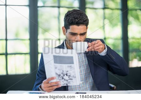 Businessman reading newspaper while having coffee in a restaurant