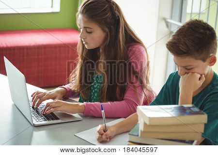 School kids doing homework in library at school