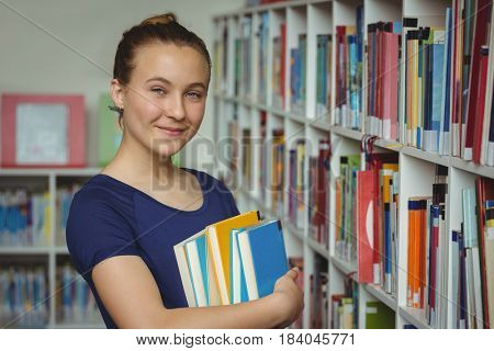 Portrait of schoolgirl standing with stack of books in library at school