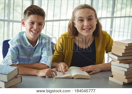 Portrait of smiling school kids reading books in library at school