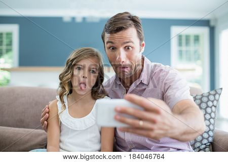 Father and daughter pulling funny faces while taking selfie in living room at office