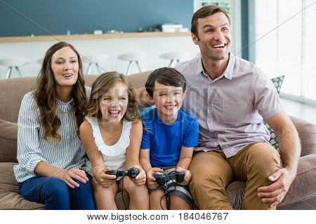 Happy family playing video games together in living room at home