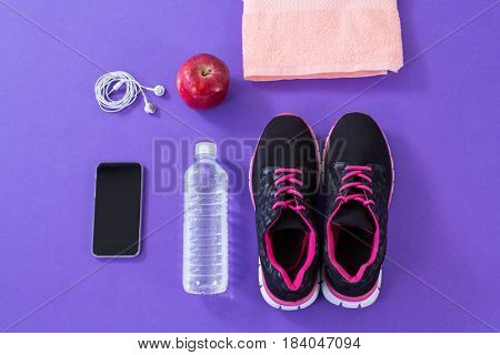 Sneakers, water bottle, towel, mobile phone with headphones and apple on purple background