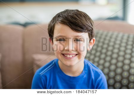 Portrait of smiling boy sitting on sofa in living room at home