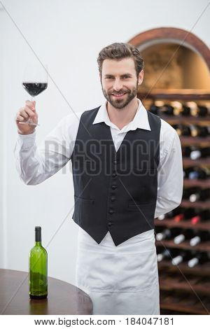 Portrait of male waiter holding wine glass in the restaurant