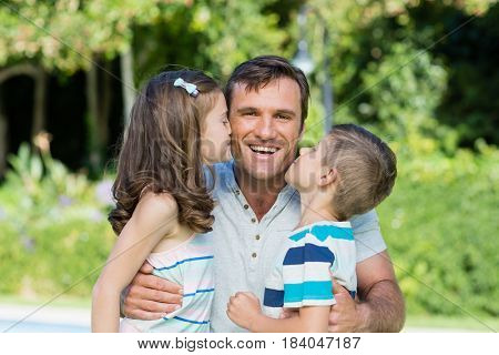 Portrait of father receiving kisses from son and daughter in the park