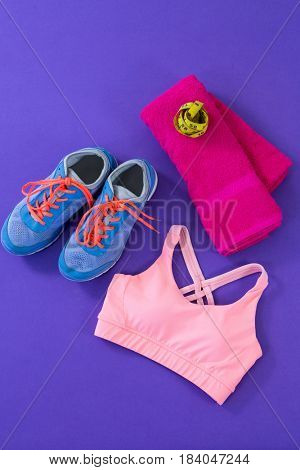 Sneakers, sports bra, towel and measuring tape on purple background