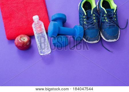 Water bottle, towel, apple, dumbbells and sneakers on purple background