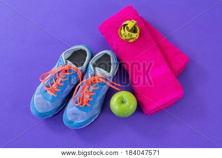 Sneakers, apple, towel and measuring tape on purple background