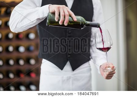 Mid-section of male waiter pouring wine in wine glass