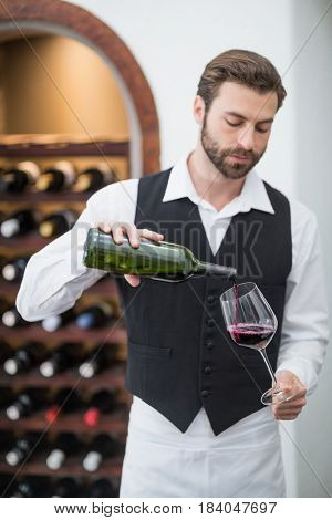 Male waiter pouring wine in wine glass in the restaurant