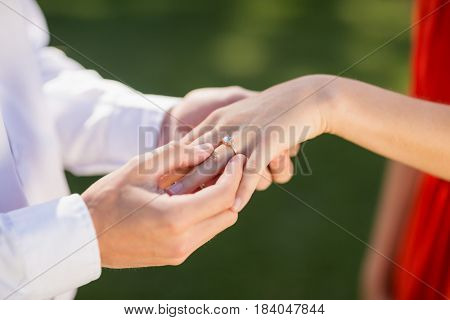 Close-up of man putting a ring on womans finger in the restaurant