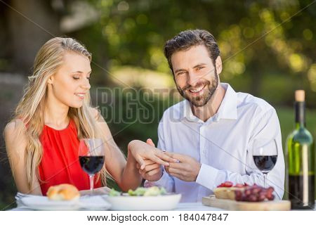 Happy man putting a ring on womans finger in the restaurant