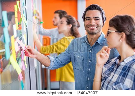 Portrait of smiling executives reading sticky notes on glass wall in office
