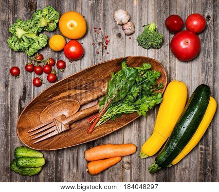 Fresh ingredients for cooking on grey rustic weathered wood background top view place for text. Sald wooden bowl. Vegan food vegetarian and healthily eating concept.