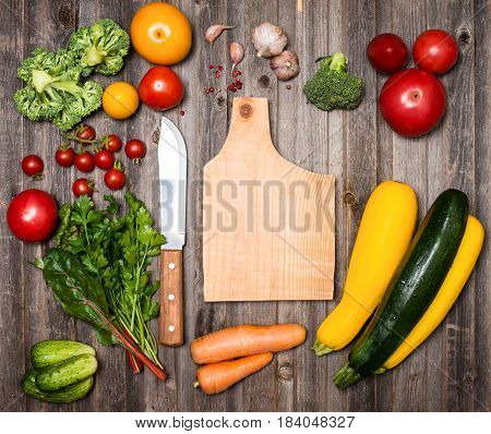 Vegetables and ingredients for cooking around cutting board on rustic weathered wood background top view place for text. Vegan food vegetarian and healthily eating concept.