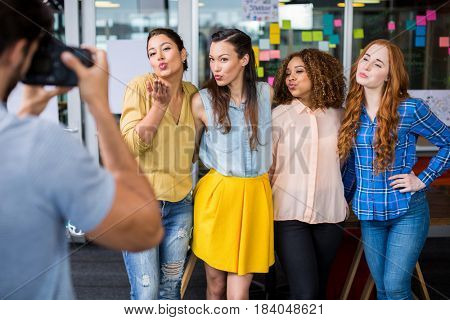 Man photographing his female colleagues with camera in office