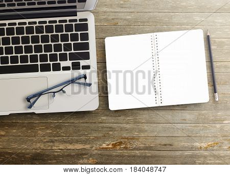 Office desk with blank notebook with black pencil and laptop computer on wooden table background. Top view with copy space for design