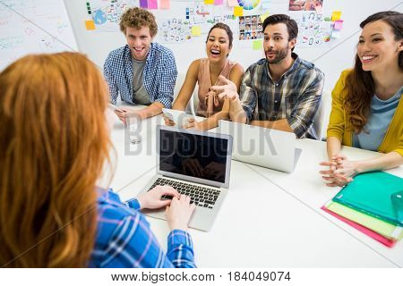 Colleagues discussing over laptop with executive during meeting in office