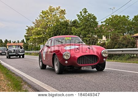 RAVENNA, ITALY - MAY 17: driver and co-driver on a vintage racing car Ferrari 250 MM Pininfarina Berlinetta (1953) in classic car rally Mille Miglia 2013 on May 17, 2013 in Ravenna, Italy