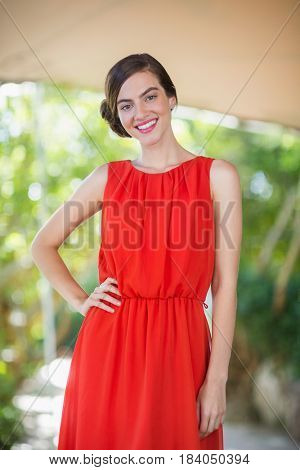 Portrait of beautiful woman standing with hands on her hip