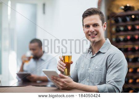 Portrait of handsome man holding beer glass while using digital tablet