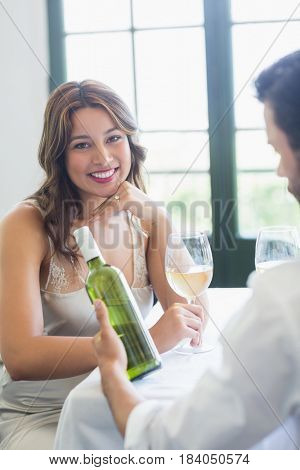 Woman smiling while holding wine glass in the restaurant