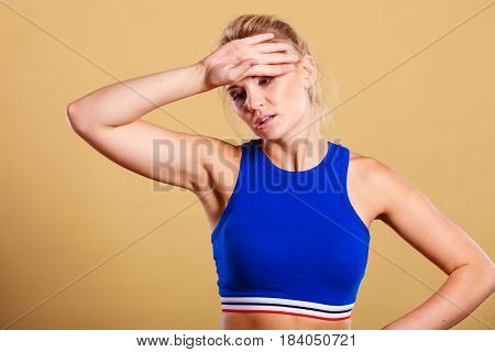 Sport training gym and health problem. Athlete fitness woman with headache migraine pain during workout. Sportswoman feeling exhausted during difficult strength training exercise.