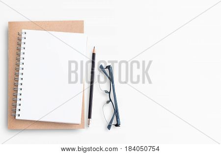 Blank paper notebook on white table background. Top view with copy space (selective focus). Office desk table concept.
