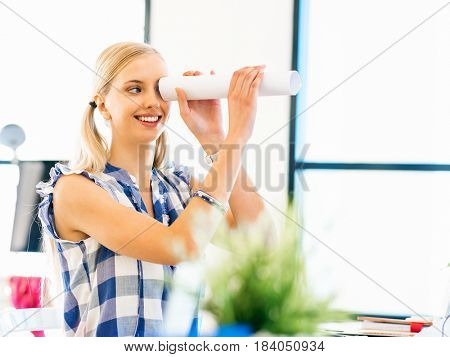 Young woman working in office holding paper tube
