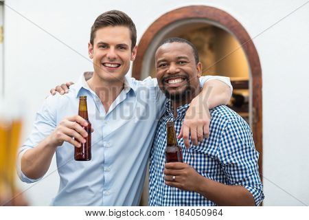 Friends hugging each other while holding beer bottles in the restaurant