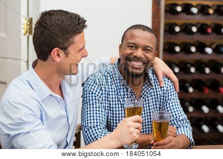 Friends laughing while having beer in the restaurant