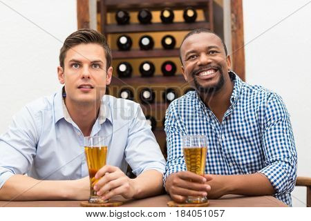 Friends watching football match while having beer in the restaurant