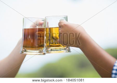 Close-up of friends toasting beer glasses