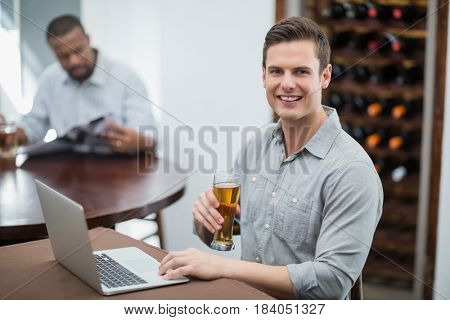 Handsome man holding beer glass while using laptop in the restaurant