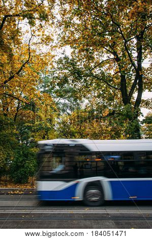 A blue public bus moves across the frame down the street with trees and foliage in the background in autumn. Abstract motion blur.