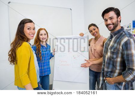 Smiling executives discussing over flip chart board in conference room meeting at office