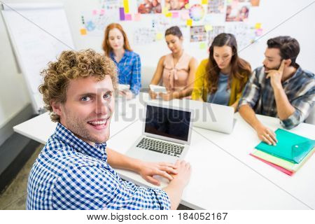 Executive discussing over laptop with his colleagues during meeting in office