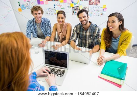 Executive discussing over laptop with her colleagues during meeting in office