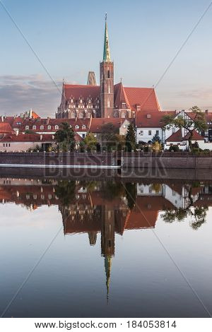 Wroclaw Poland 22nd october 2016. Church of the holy cross (St Bartholomew) on Ostrow Tumski (Cathedral Island) reflected in the Odra river at dawn.
