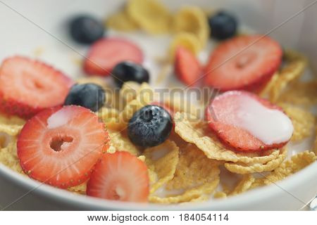 closeup of healthy breakfast with corn flakes and berries in white bowl, slightly toned photo