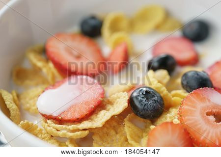 closeup of healthy breakfast with corn flakes and berries in white bowl, macro shot