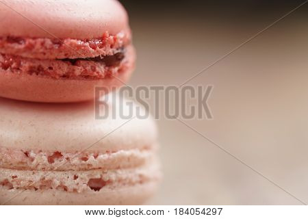 closeup shot of pink pastel colored macarons on wood table, vintage toned photo