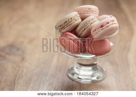 macarons with strawberry, rose and caramel flavour in glass bowl, shallow focus