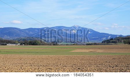 landscape of Beskydy mountains with remnants of snow on the hills and fields under them in spring, Czech Republic