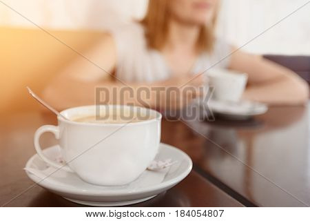 Selective focus on a cup with aromatic coffee. Blurred background with girl drinking coffee cup.