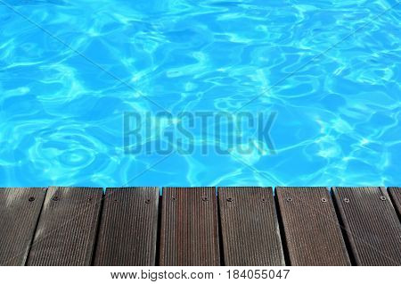 Wooden deck and clear turquoise water with ripples and copy space