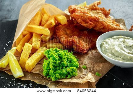 British Traditional Fish and chips with mashed peas, tartar sauce on crumpled paper
